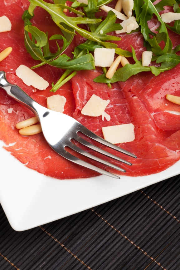 Carpaccio auf einem Teller mit Parmesan und Pinienkernen