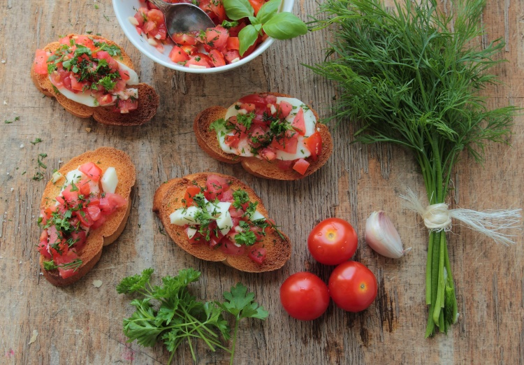 Bruschettas with fresh tomato, garlic, mozzarella and herbs
