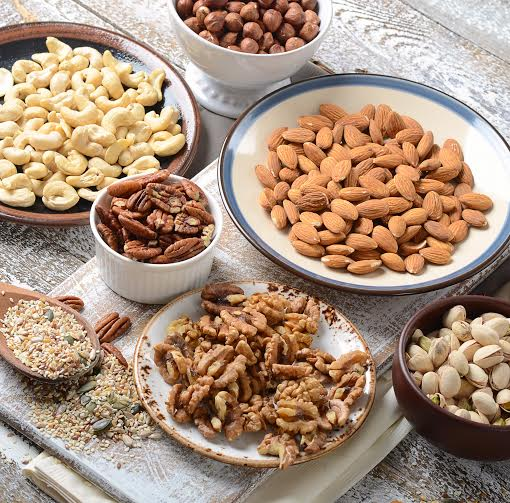 Assorted mixed nuts on a wooden board.